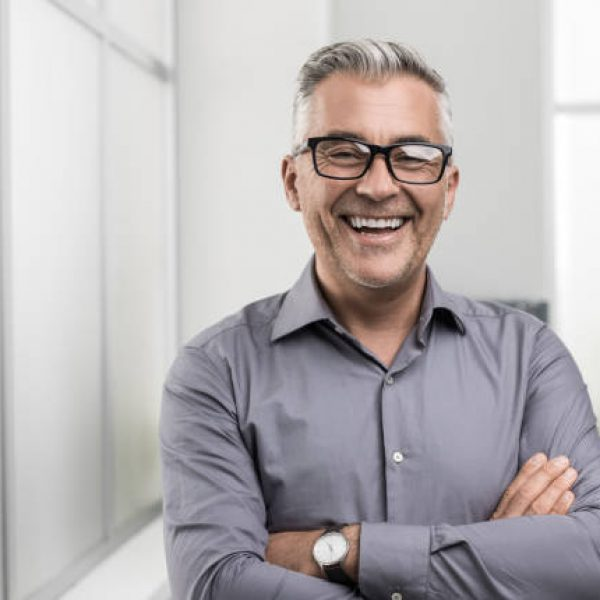Confident businessman posing in the office with arms crossed, he is smiling at camera